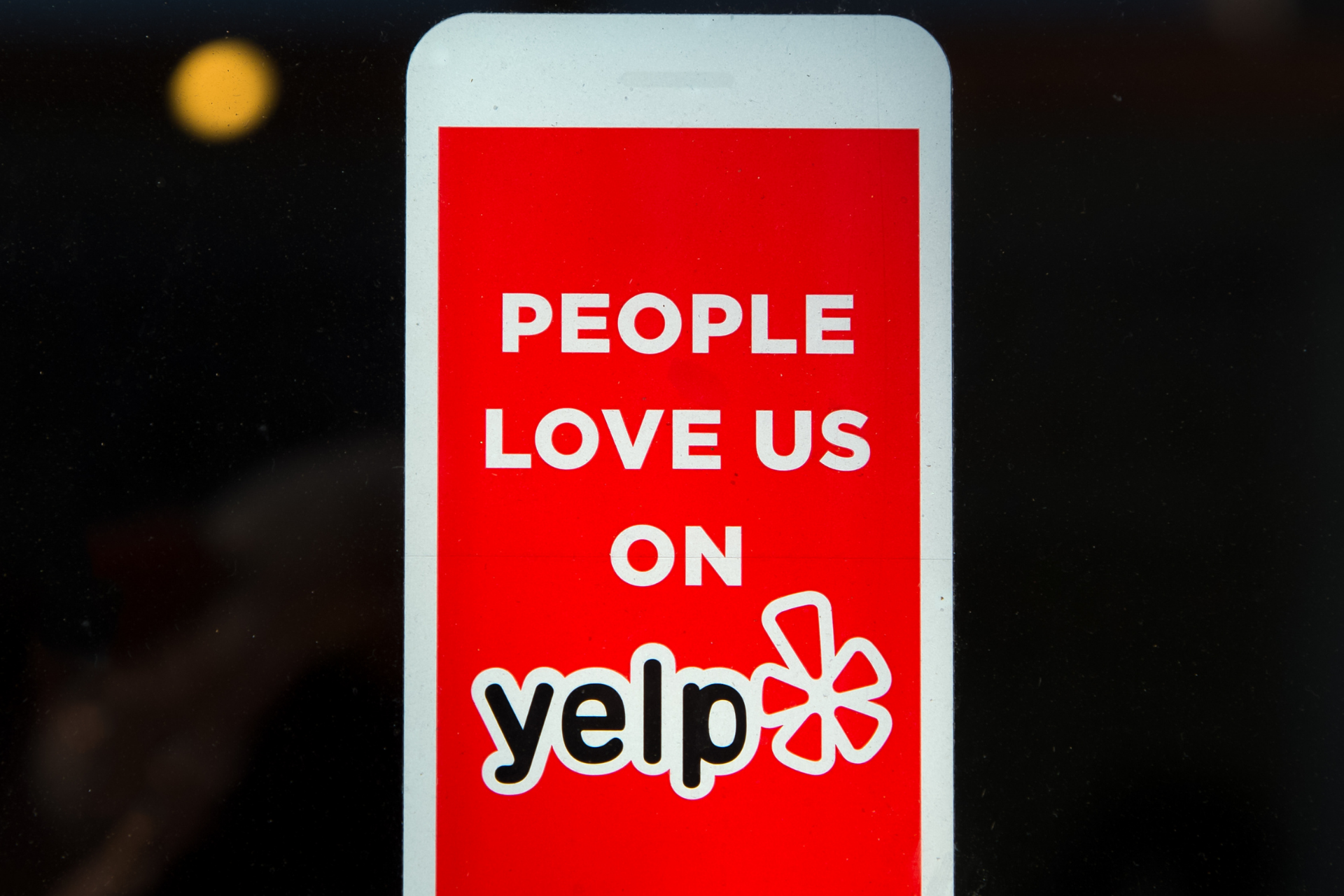 A sign displaying people love us on yelp.