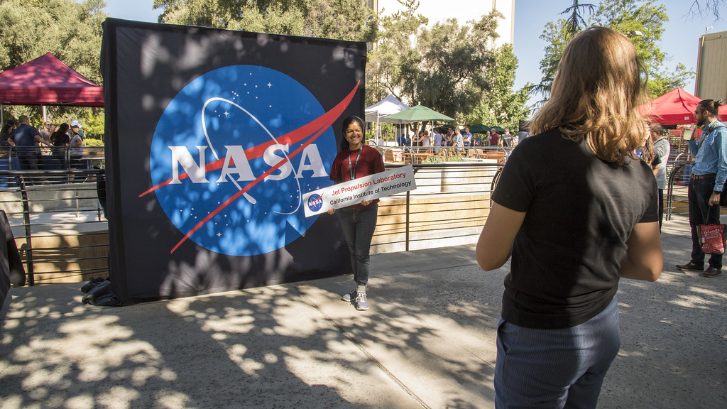 A young girl stands in front of a large NASA logo as another girl takes her photo.