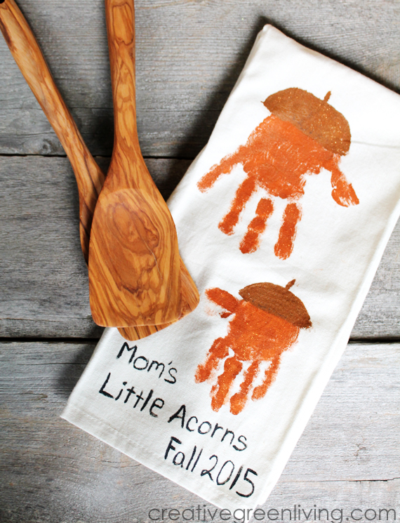 white dish towel with children's handprints in paint. text reading mom's little acorns fall 2015. the towels sit on a table next to wooden spatulas