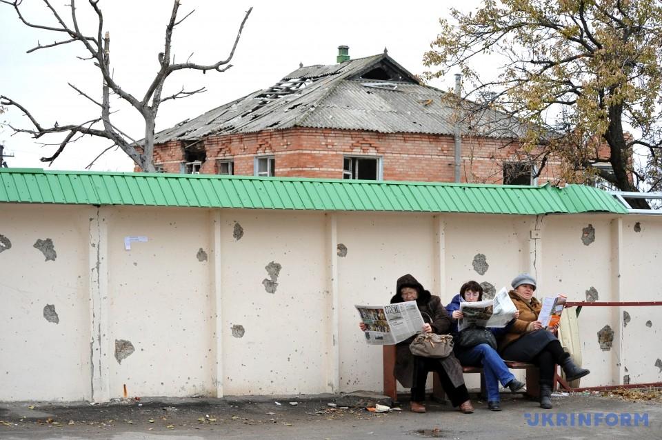 Женщины читают прессу на фоне разрушенного в результате обстрелов дома в пгт Станица Луганская, 27 октября 2015 года. Фото: Станислав Михайлов/Укринформ