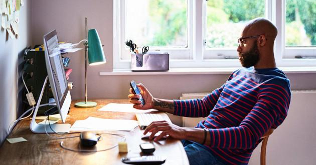 Man working on laptop and mobile device from home: remote work policy