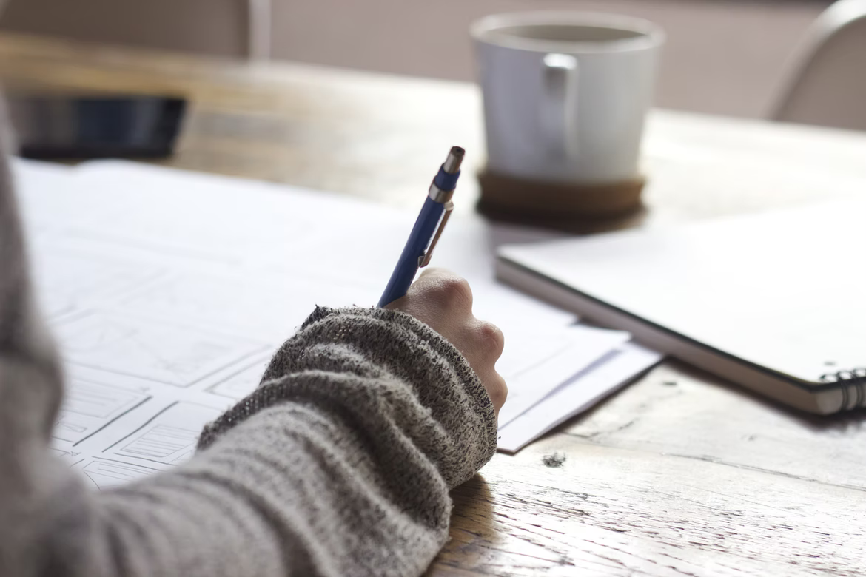 žena vo svetri píše na papier, v pozadí je notes a šálka