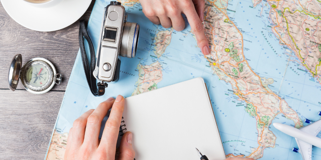 Planning a trip with a map, a notebook and a camera
