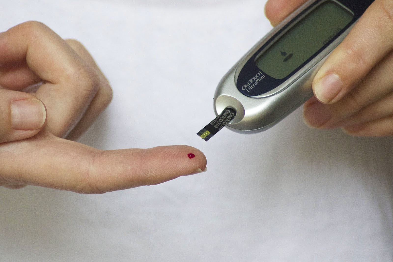 A person testing the blood sugar levels