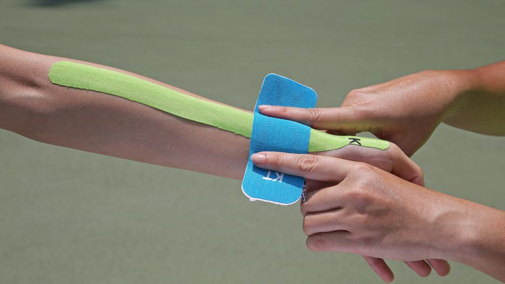 Step4.以兩手食指幫助固定肌內貼位置,手指範圍內則為50%拉力區。