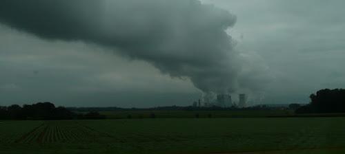 Die Wasserdampfwolke und giftige Abgase eines Braunkohlekraftwerkes ziehen über die grüne Landschaft und eine riesige Steinwüste mit grossen Baggern.