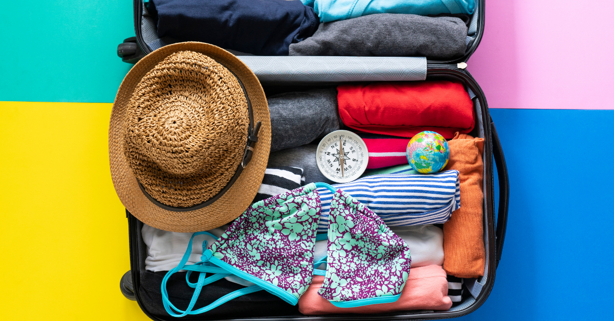 A suitcase with organized clothes, a hat and a bathing suit
