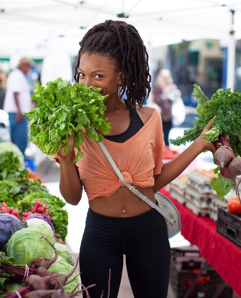 Jenné Claiborne shopping for vegetables at an outdoor market