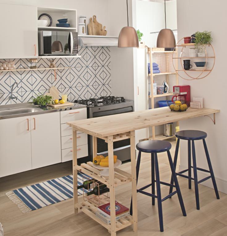 Cozinha com azulejos com linhas azuis, prateleira de pínus de madeira dialoga com a bancada, lâmpadas pendentes, armário branco com detalhes bronze e piso de madeira.