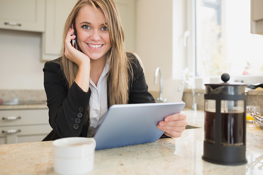 Young smiling woman holding tablet and talkijng on the phone after finding a home for sale on the MLS VA
