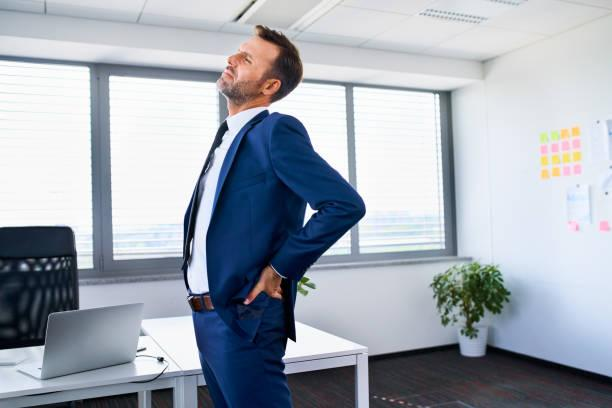 Lower back pain. Businessman stretches in office. Lower back pain. Businessman stretches in office. low back pain stock pictures, royalty-free photos & images