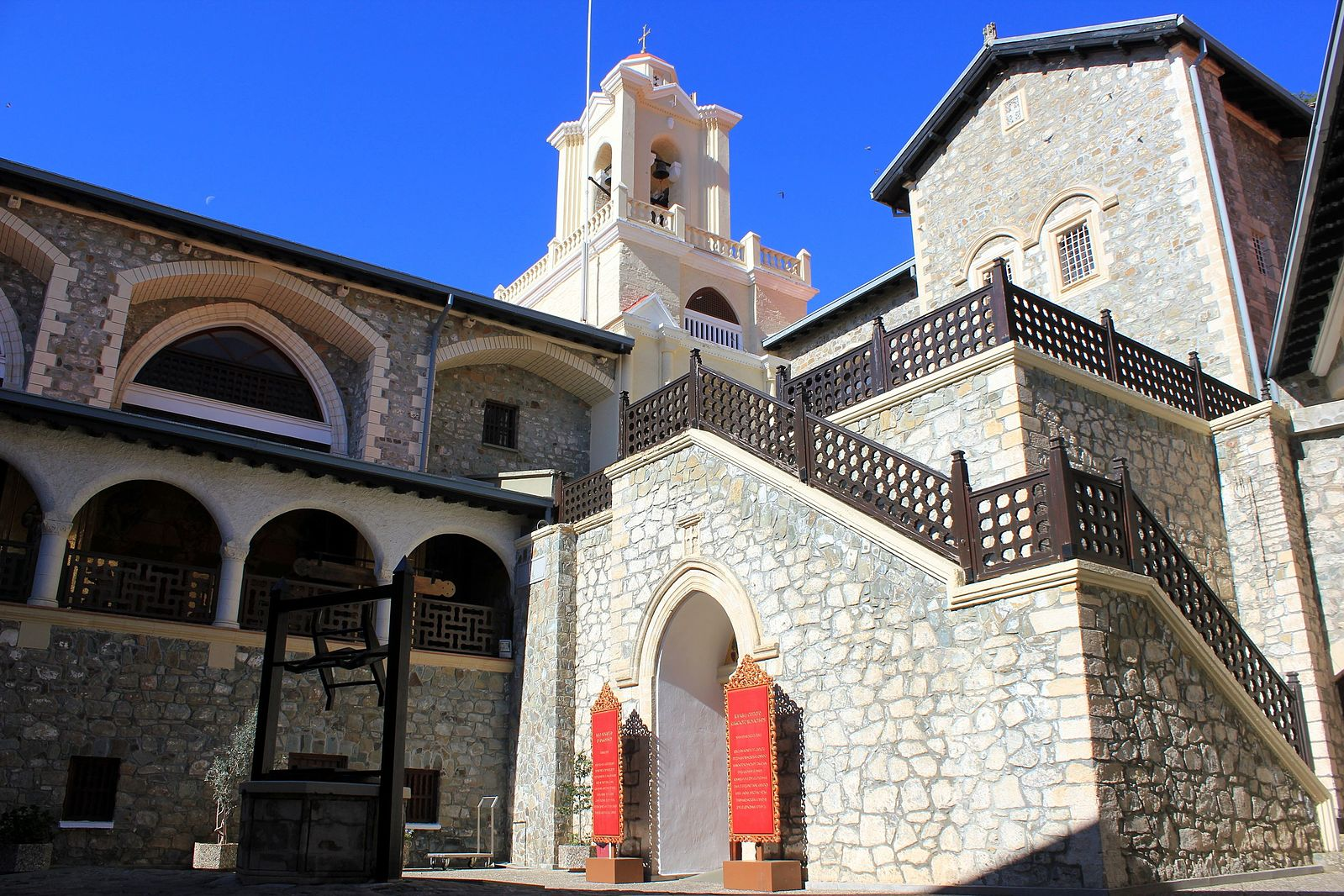 kykkos monaster. whitewashed stone architecture, outdoor staircase and large belltower. sunny day in kykkos monastery cyprus