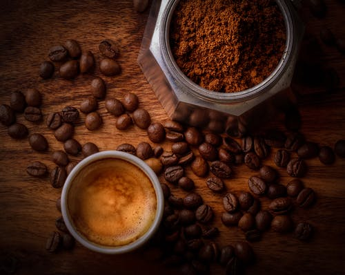A cup of espresso surrounded with coffee beans and next to a jar of grounded coffee by janko Ferlic.