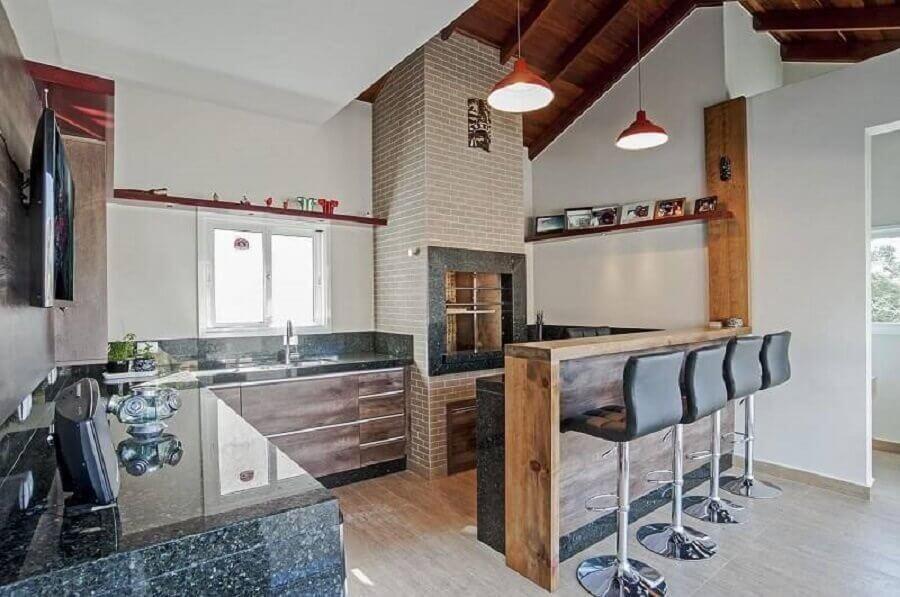 Área de lazer fechada de casa com churrasqueira de alvenaria, bancada toda de granito preto, e bancada de madeira e bancos pretos, piso amadeirado e luminárias pendentes.