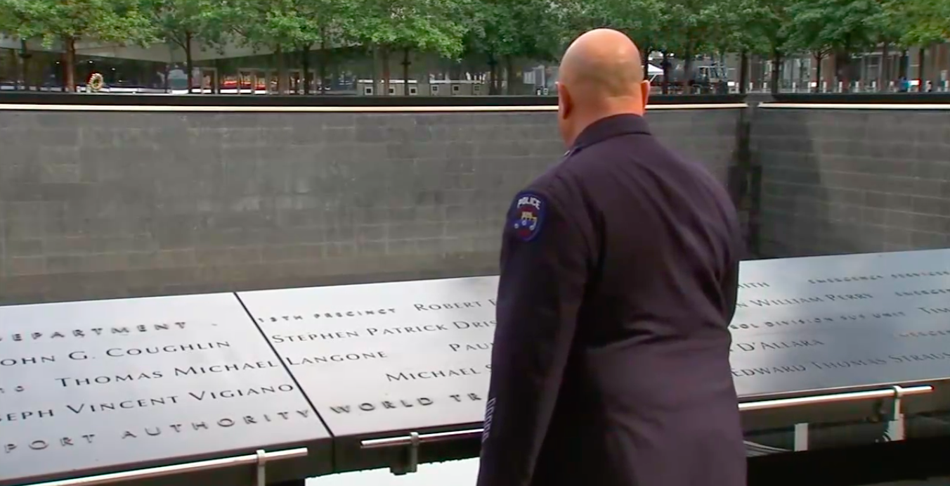A police officer stands beside the 9/11 memorial