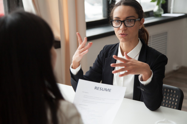 Confident millennial female applicant in glasses talking at job interview Free Photo
