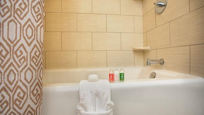 Folded towels and toiletries on the edge of a bathtub-shower