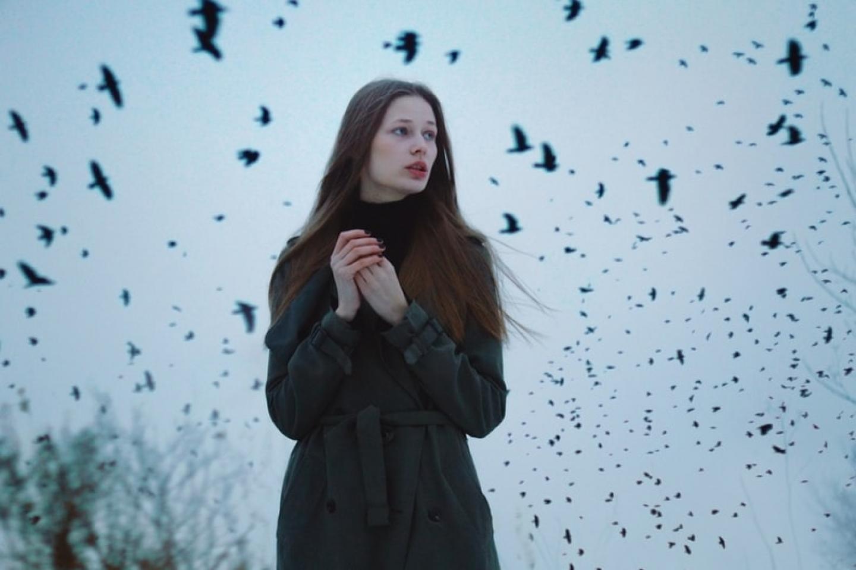 Photo d'une femme sur un arrière-plan de ciel qui pullule de corbeaux