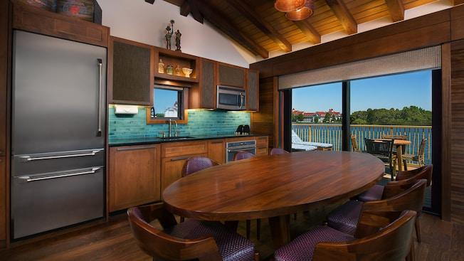 A modern kitchen overlooking Seven Seas Lagoon that features a dining table, refrigerator and chairs