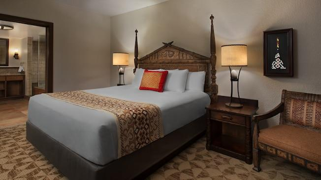 An African-themed bedroom with a bed, side tables with ornate lamps, chair, wall art and a bathroom