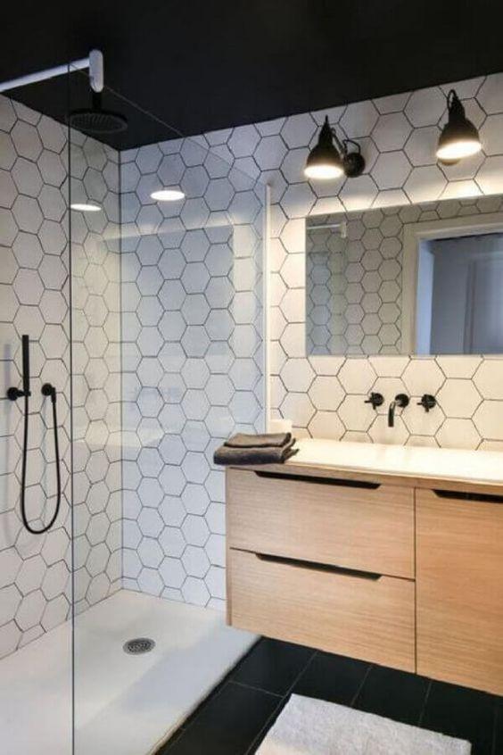 Banheiro com azulejo hexagonal branco por todo banheiro, piso branco na area do box e piso preto fora, armário amadeirado com pia branca, torneira e chuveiro preto e espelho retangular