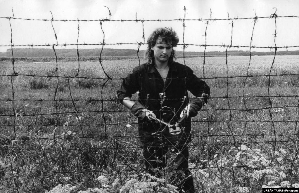 """Человек режет забор из колючей проволоки на границе между Венгрией и Австрией в 1989 году. В апреле 1989-го в заграждении отключили электрический ток, часть его позднее разобрали, и """"железный занавес"""", отделявший Восток от Запада, начал рушиться"""