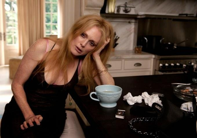 Julianne Moore as Havana in 'Maps to the Stars' (2014). Havana looks haggard, with dark eyes as she rests her head on her hand, propped up on the kitchen counter with a large mug and some used tissues beside her.