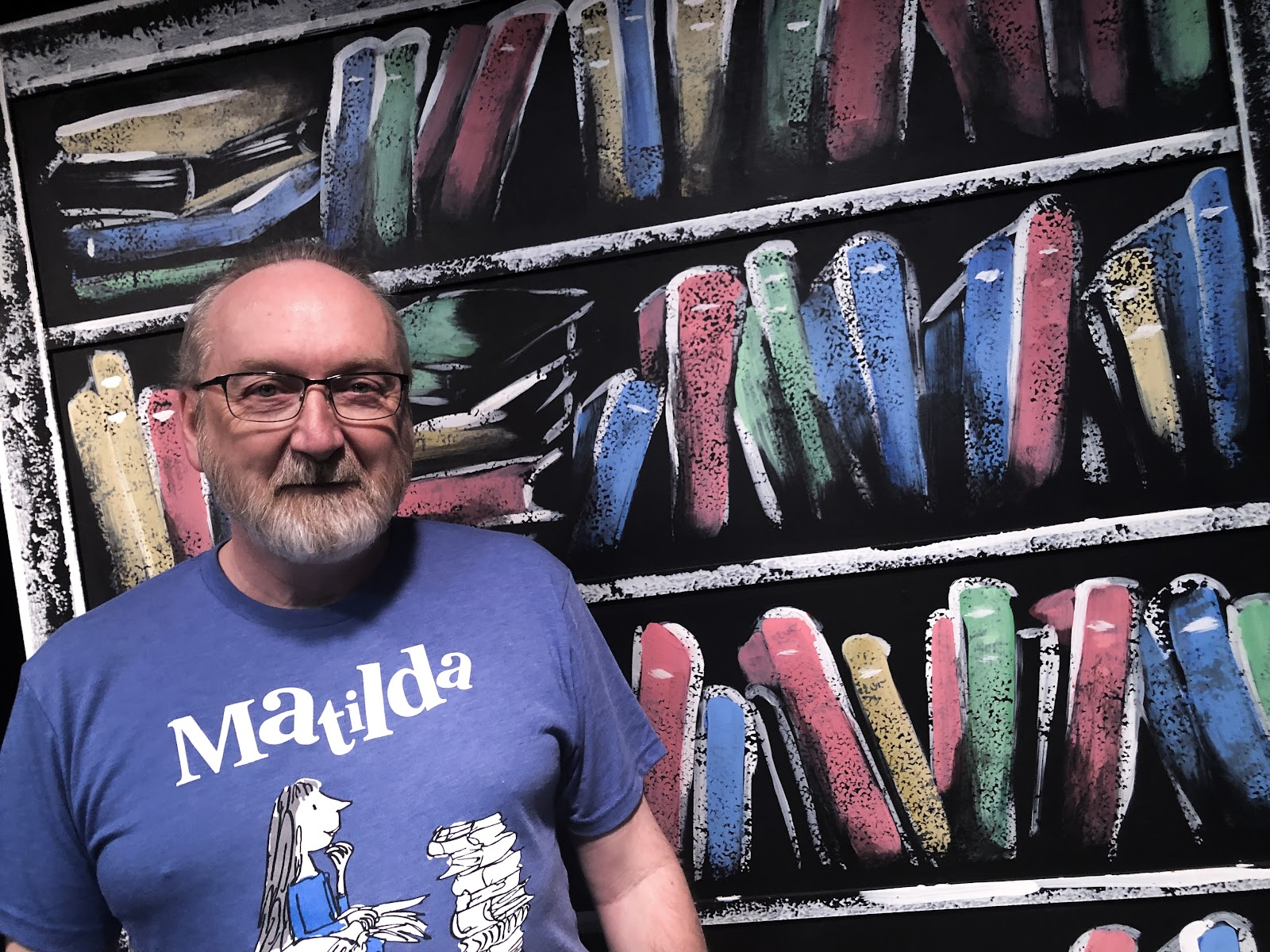 Michael Flowers, Director of Red Mountain Theatre Company's Matilda The Musical, stands by bookcase prop