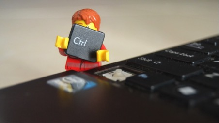 Lego man holding the control button off a computer keyboard.