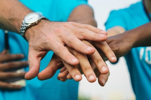 Volunteers stacking their hands together before working together