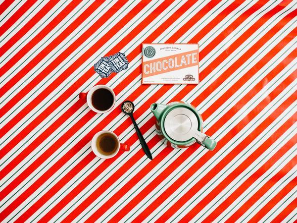 foto em um fundo listrado com um bule, caneca de café e chocolate