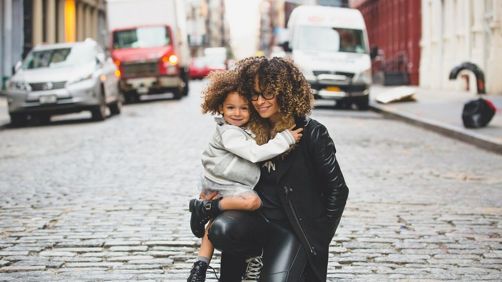 An urban woman holding her child on an urban, cobblestone street.