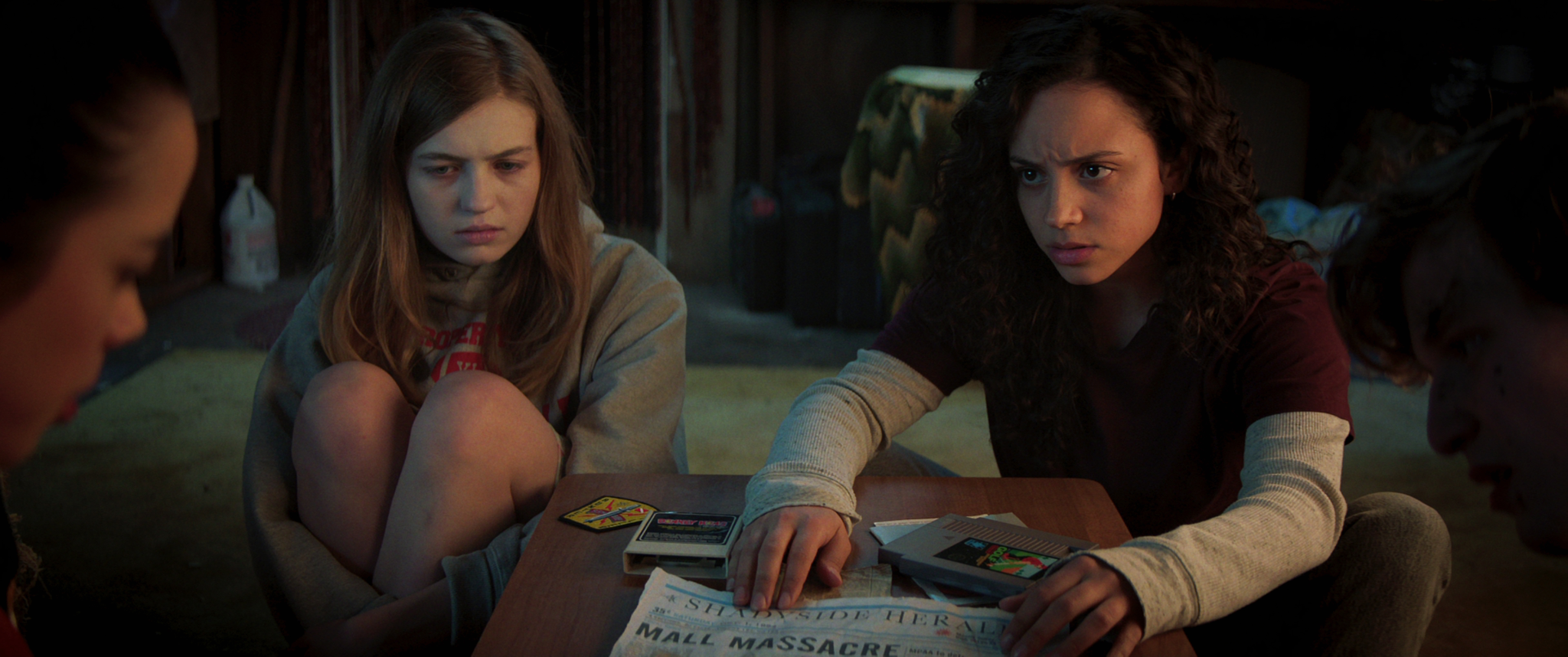 Still from Fear Street part 1. Sam and Deena sit on the floor, as Deena pushes a newspaper headline across the table to another friend, mostly out of the frame. Sam hugs her knees, looking afraid, and Deena seems concerned.