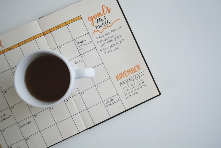 cup of coffee on top of calendar note book