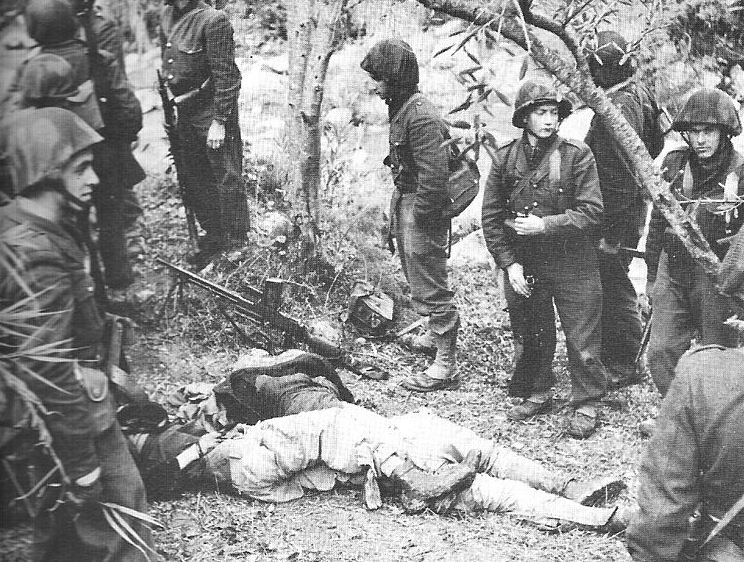 French soldiers standing nonchalantly next to the bodies of Algerians.