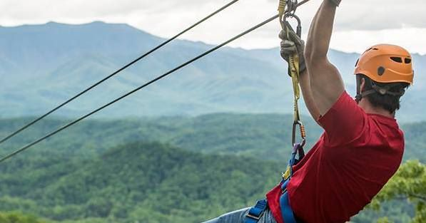 Man in red shirt looking at mountains while ziplining