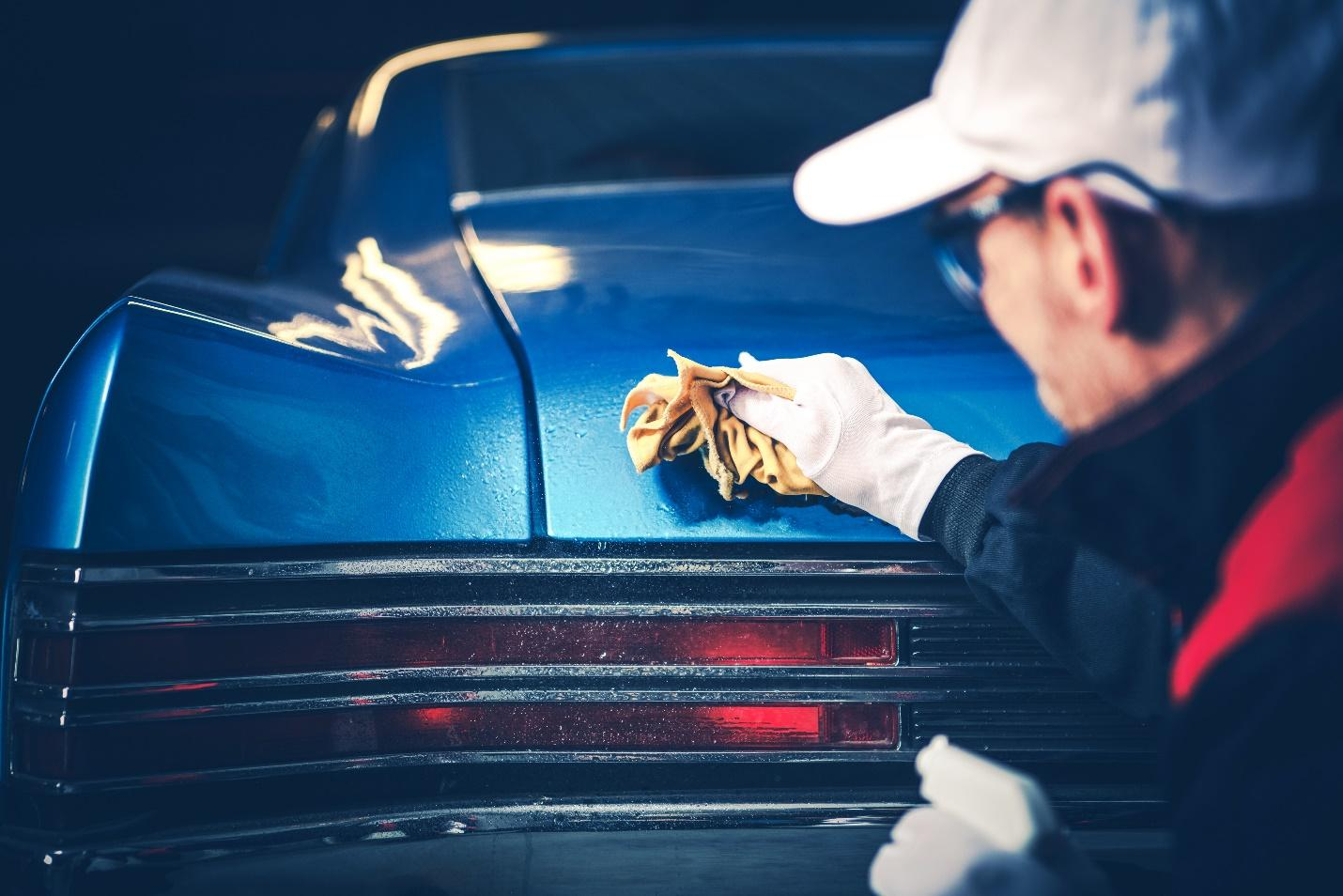 A man doing a DIY ceramic coating on a classic car.