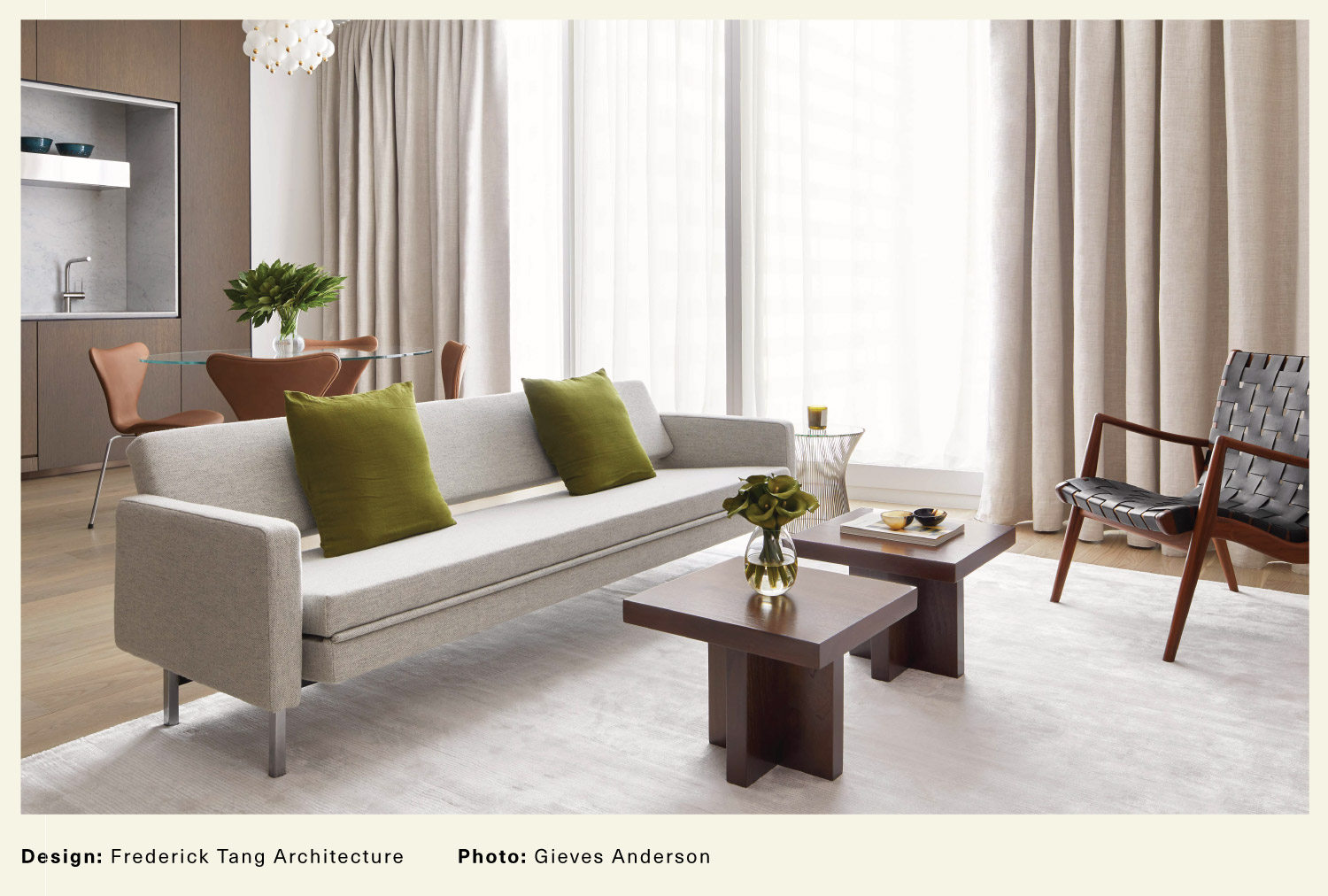 Modern living room with a gray couch, brown coffee tables, and a large window