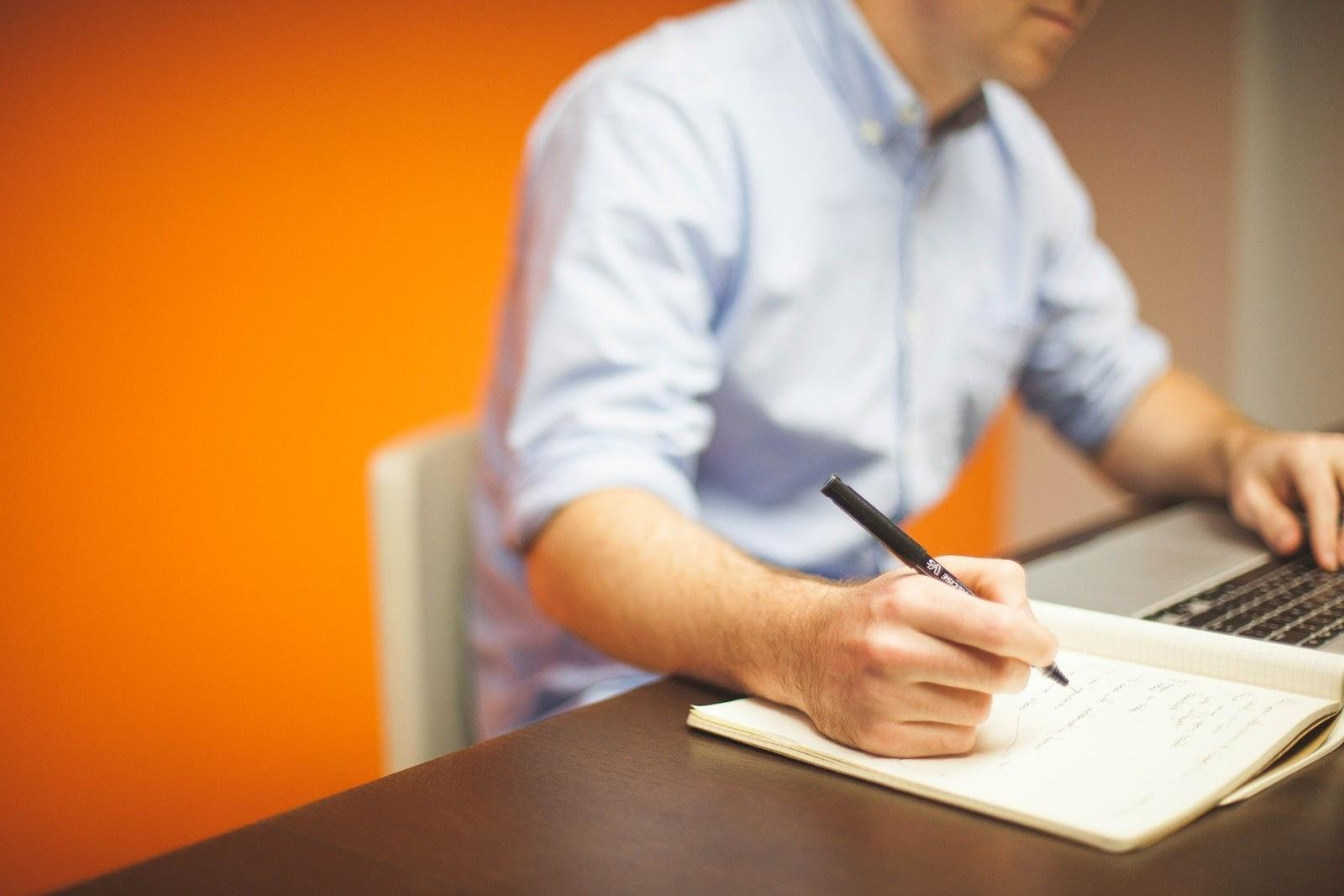Uma pessoa escrevendo em um caderno.