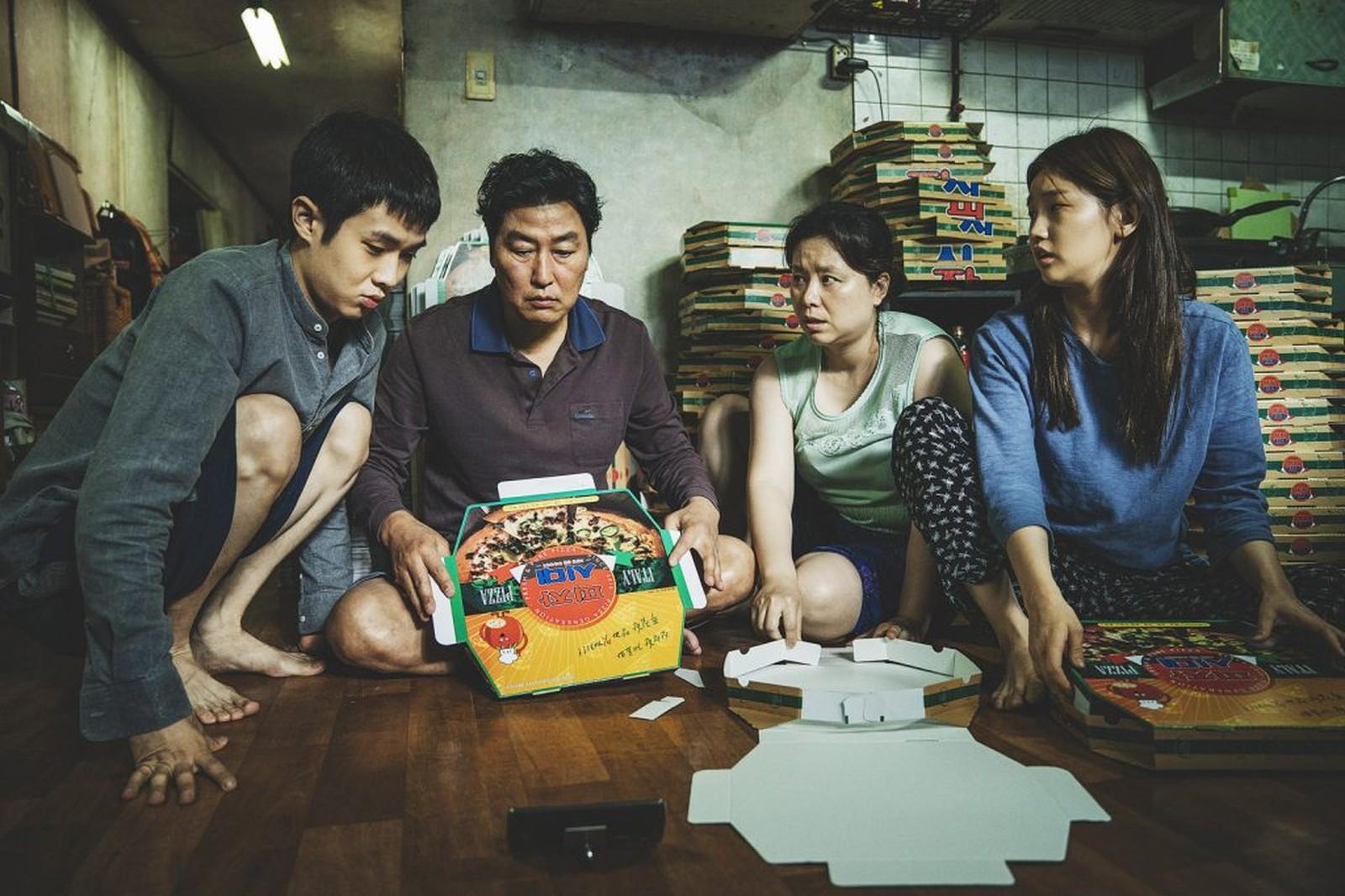 Personagens em uma cena de uma das indicações de filmes para o óscar segurando jogo no chão de um cômodo.