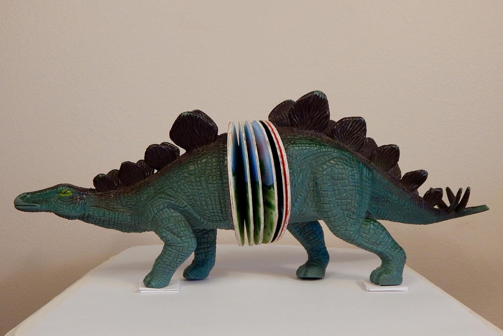 "4"" x 17"" Mixed Media: repurposed children's book, toy stegosaurus, paint, paper, colored pencil."