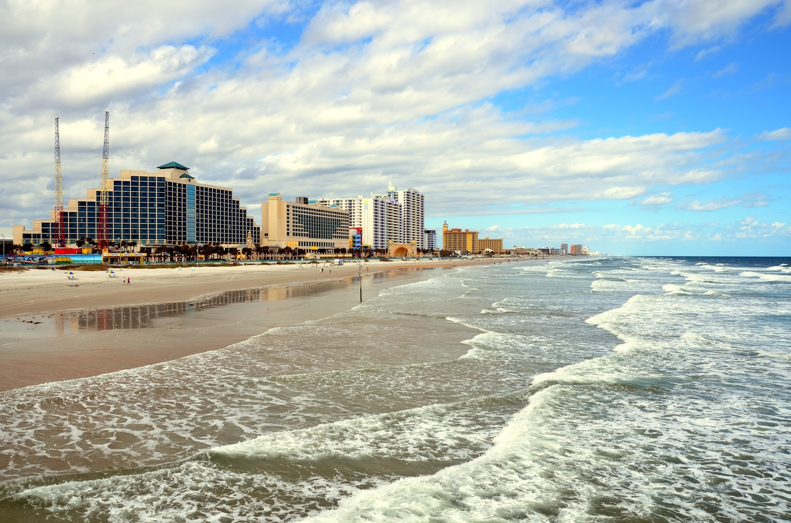 wide sandy beach small waves clean blue water and hotels in background in daytona beach florida
