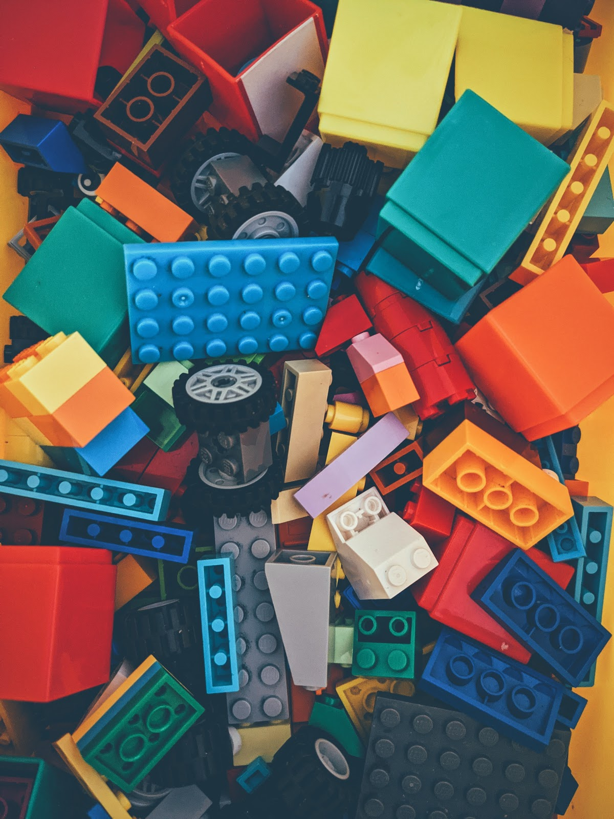 Lego-like building bricks, as well as wheels and axles of many colors lay in a jumbled pile.
