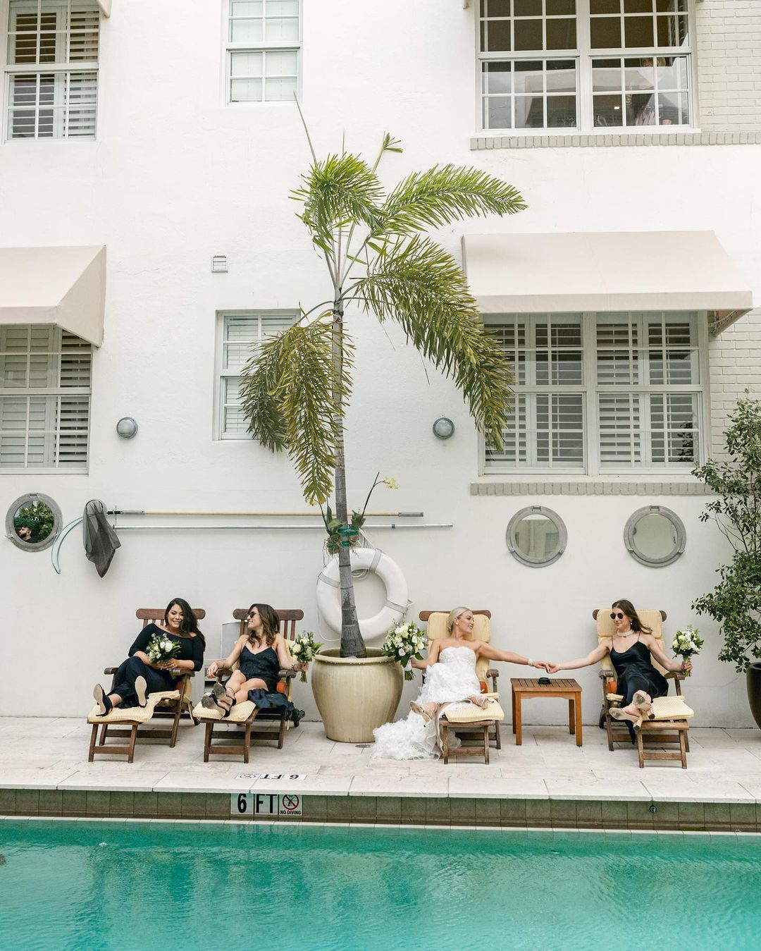 The bride and her bridesmaids relaxing by the pool