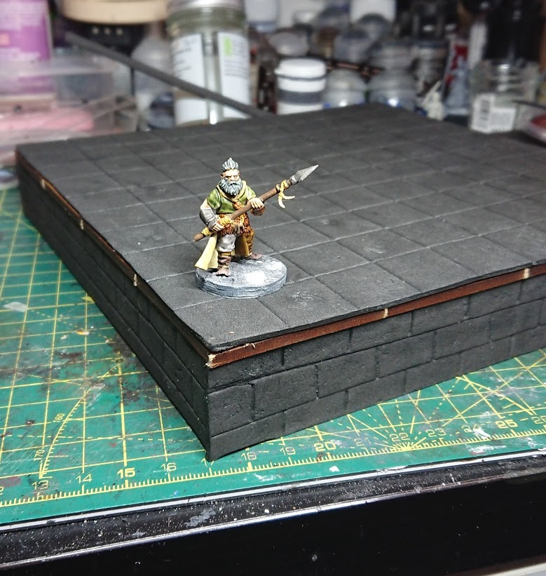 A Frostgrave barbarian on a square riser that has been clad in EVA foam.