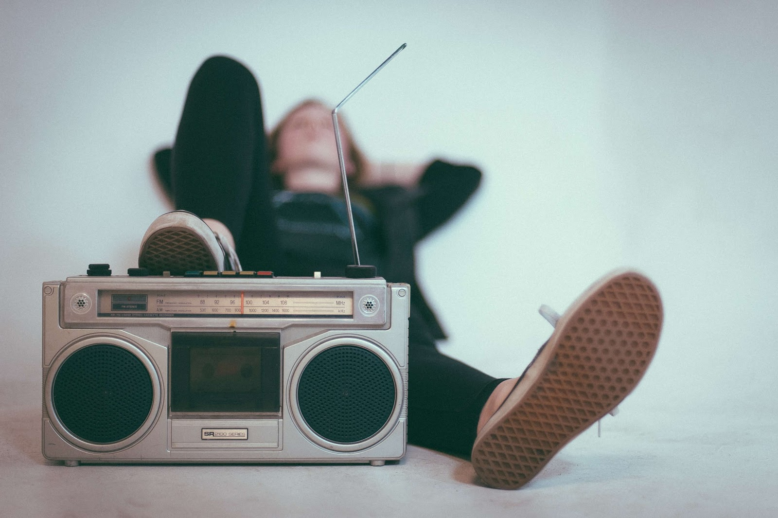 A person lying down with their foot rested on a portable radio