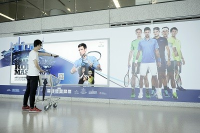 Billboard in airport with tennis players and a QR code to scan.