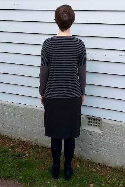 Siobhan stands in front of a weatherboard house. She wears a drop shoulder knit tee with grey/black striped body and concrete grey neckband and sleeves, with black straight knee length skirt, black leggings and ankle boots. Her back is to the camera.