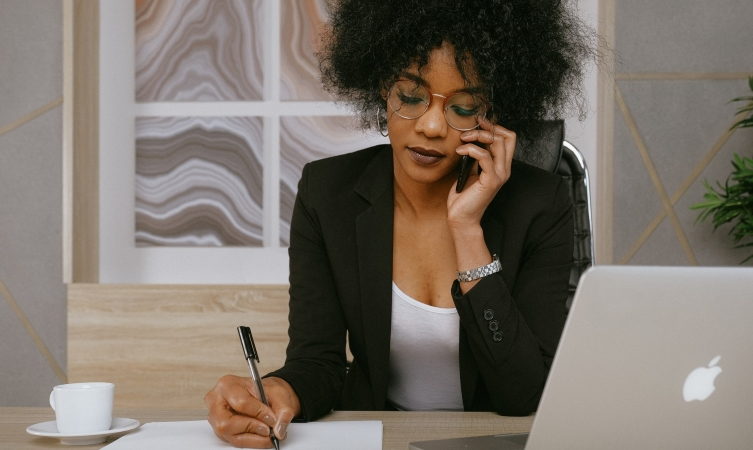 woman talking on her phone and taking notes