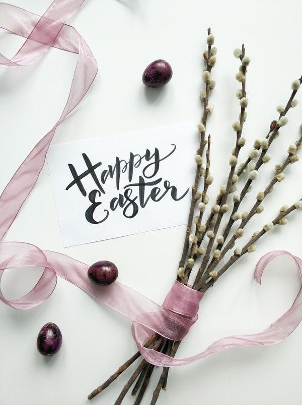 """uma imagem com um papel escrito """"happy easter"""" ao lado de um ramalhete de flores enrolado por uma fita rosa"""